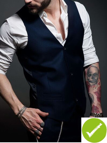 Inked dude in waist coat, key chain, watch and white shirt with sleeves rolled up.