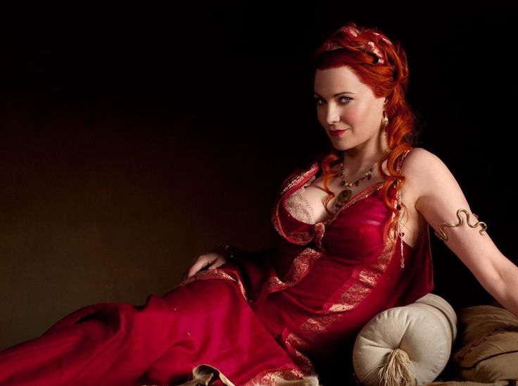 Smouldering Lucy Lawless reclining in red in opulent Greek dress costume from Sparticus.